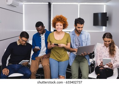 Portrait of young businesswoman with colleagues using various technologies at office