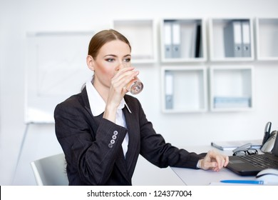 Portrait of young businesswoman drinking water at office