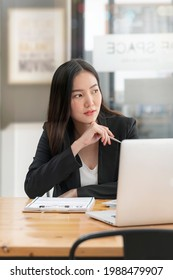 Portrait of young businesswoman with hand touc her chin and siiting at office desk, veritcal view.