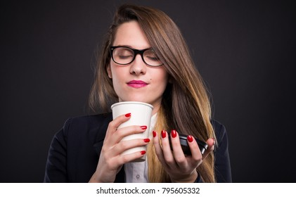 Portrait of young businesswoman holding and enjoying the fresh smell of coffee