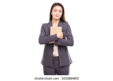 Portrait of young businesswoman holding stack book