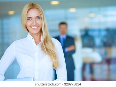 Portrait of young businesswoman with laptop in office with colleagues in the background