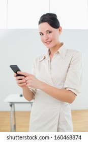 Portrait of a young businesswoman with mobile phone in a bright office
