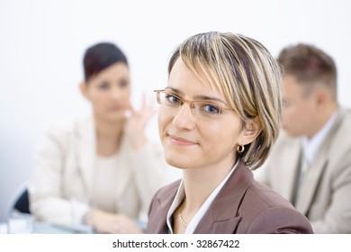 Portrait of young businesswoman in office. Business people working in background.