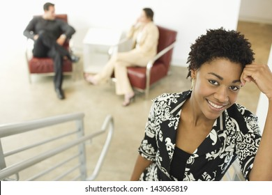 Portrait of young businesswoman on stairway with colleagues sitting on chairs in background