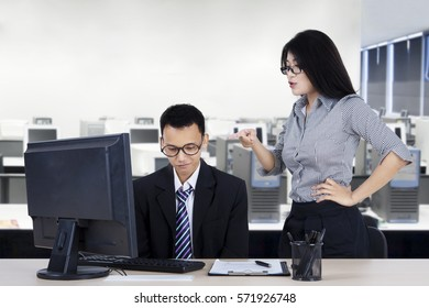 Portrait of young businesswoman shouting to her employee while pointing to computer in the office
