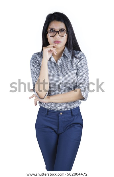 Portrait of young businesswoman showing angry expression while standing in the studio, isolated on white background