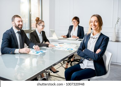 Portrait of a young businesswoman sitting during the conference with colleagues in the office