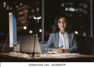 Portrait of a young businesswoman sitting at her desk using a laptop and writing notes while working overtime in an office late in the evening