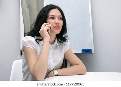 Portrait of young businesswoman sitting and talking phone at workplace. Pretty girl in business clothes talking at white table. Place for text on the board