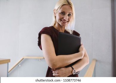 Portrait of young businesswoman standing in the office holding file. Caucasian female in office looking at camera and smiling.