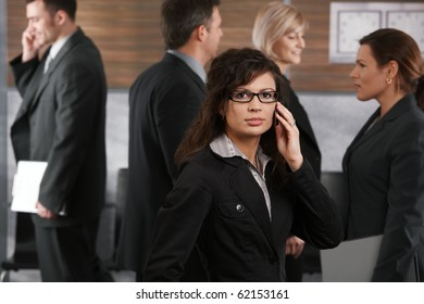 Portrait of young businesswoman standing in office lobby, talking on mobile phone.?