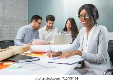 Portrait of young businesswoman taking notes on meeting with business partners and looking at camera in office.