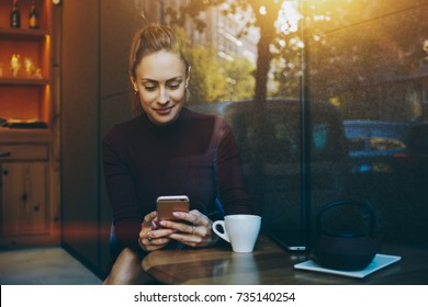 Portrait of young businesswoman use mobile phone while sitting in comfortable coffee shop during work break, charming happy female reading fashion news on cell telephone during breakfast in restaurant