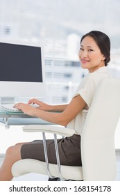 Portrait of a young businesswoman using computer in a bright office