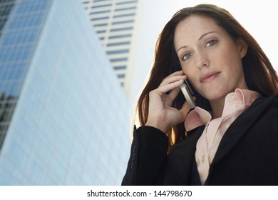 Portrait of a young businesswoman using mobile phone against office building