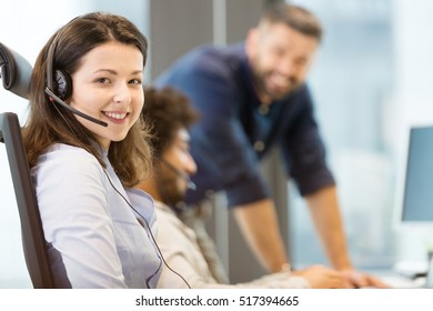 Portrait of young businesswoman wearing headset with colleagues in background at office