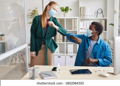 Portrait of young businesswoman wearing mask bumping elbows with African-American man as contactless greeting in post pandemic office, copy space