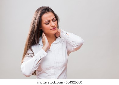 Portrait of young businesswoman who is having pain in her neck.