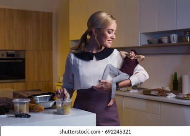 Portrait of a young businesswoman  woman which feeds her boyfriend with soup in their kitchen. She came after work day and he spent whole day at home