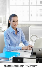 Portrait of young businesswoman at work, smiling confidently at camera, using laptop computer at desk.?
