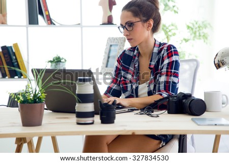 Portrait of young businesswoman working in her office with laptop.