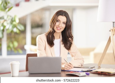 Portrait of a young businesswoman working on laptop and doing some financial calculations while sitting in her workstation.