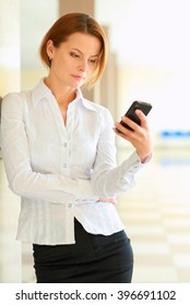 Portrait of young busineswoman standing with phone in office lobby