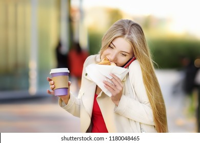Portrait of young busy woman in the big city. Girl eating snack, drinking coffee and answering a phone call. Multitasking concept
