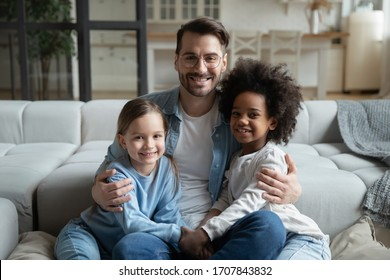 Portrait of young caring father sit on couch hug cuddle with small multiracial daughters, happy Caucasian dad embrace play with multiethnic little children, enjoy family weekend at home together