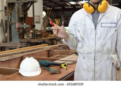 Portrait of young carpenter in white safety uniform holding a pencil in hands in wood workshop background. Industrial concept.