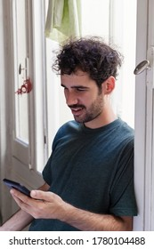 Portrait of young casual alternative model with moustache and curly hair using smartphone on a window indoors with natural light focused browsing internet.