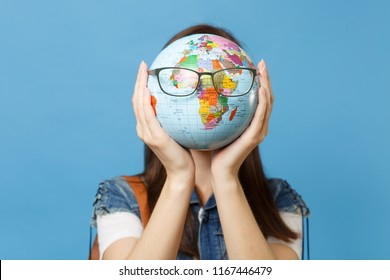 Portrait of young casual brunette woman student in denim clothes holding and hiding behind world globe with glasses isolated on blue background. Education in high school university college concept