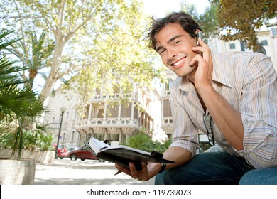 Portrait of a young casual businessman using a hands free ear device to have a conversation while sitting outdoors near classic buildings in the city.
