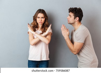 Portrait of a young casual couple standing together isolated over gray wall background, man asking for something and woman refuses