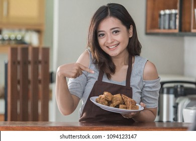 Portrait of a young casual girl smiling through the camera in the kitchen