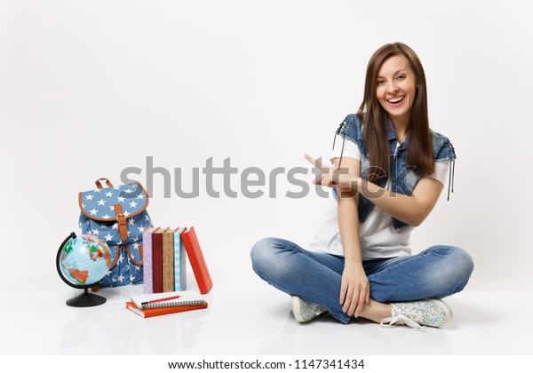 Portrait of young casual laughing woman student in denim clothes sitting pointing index finger on globe backpack school books isolated on white background. Education in high school university college