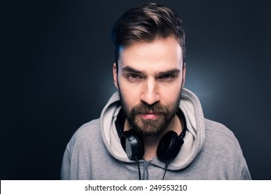 Portrait of young casual man with headphones around the neck. Studio shot on gray background.