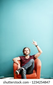 Portrait of a young caucasian bearded man with long hair showing with hands on the colorful background sitting on the chair. Image with copy space
