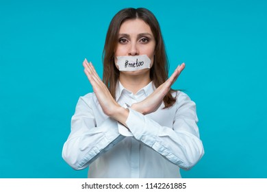 portrait of young caucasian brown-haired girl demonstrates by hands the prohibition sign, the mouth is sealed with a white plaster with an inscription #metoo. Text space. #metoo movement concept.