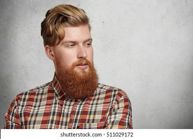 Portrait Of Young Caucasian Brutal Man With Fuzzy Beard Wearing Red  Checkered Shirt Looking Away With