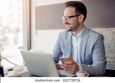Portrait of young caucasian businessman in casual shirt and glasses using laptop computer at workplace.