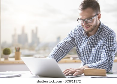 Portrait of young caucasian businessman in casual shirt and glasses using laptop computer at workplace