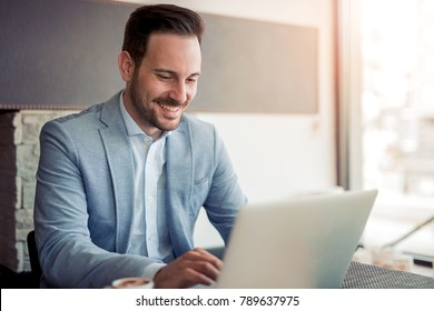 Portrait of young caucasian businessman in casual shirt  using laptop at workplace.