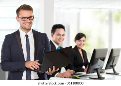 A portrait of a young caucasian businessman, with his team behind holding laptop. isolated in white background
