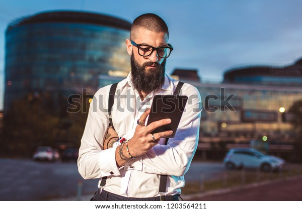 Portrait of a young caucasian businessman holding a digital tablet outdoor.