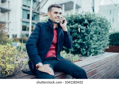Portrait of young Caucasian businessman wearing coat sitting on bench and talking on mobile phone consulting customer. Work outside concept