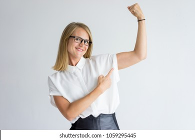 Portrait of young Caucasian businesswoman or student wearing glasses and white shirt showing muscles and smiling at camera. Woman leader, feminism concept