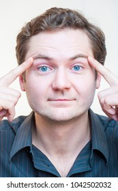 Portrait of young Caucasian Ethnicity blue-eyed man points on his eyebrows on white background. Human face parts.
