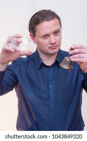 Portrait of young Caucasian Ethnicity man ringing a small bell in one hand calling for service with empty alcohol glass in other hand on white background.